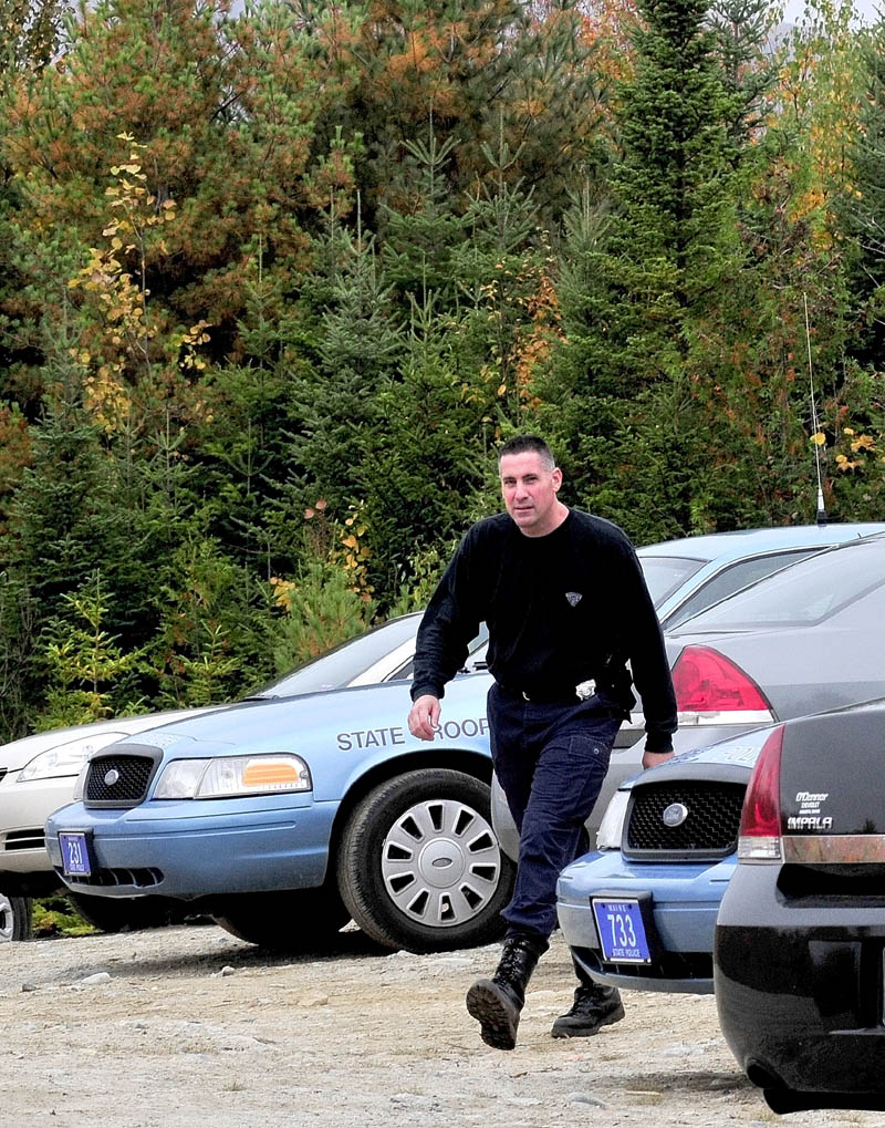 State police Sgt. Troy Gardner exits a Major Crimes Unit command post in the woods off the Rowe Pond Road in Pleasant Ridge as investigators combed the nearby woods.