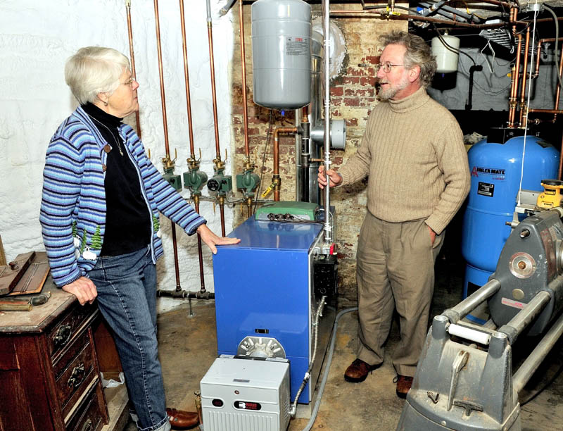 The Revs. Alice and David Anderman speak about the weatherization program they participated in beside a new energy-efficient furnace, hot water tank and foam insulation-covered walls in the basement of their home in Waterville.