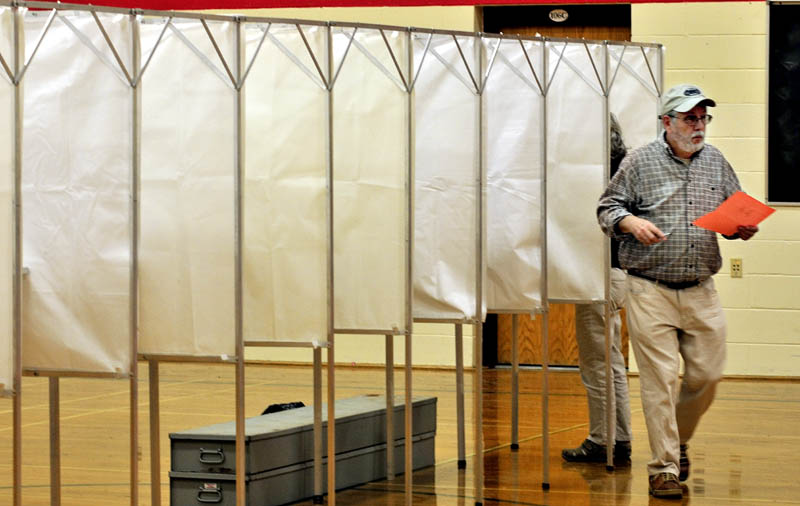 CIVIC DUTY: Frank Gifford exits an election booth after voting on the RSU 18 school budget at the Williams School in Oakland on Tuesday.