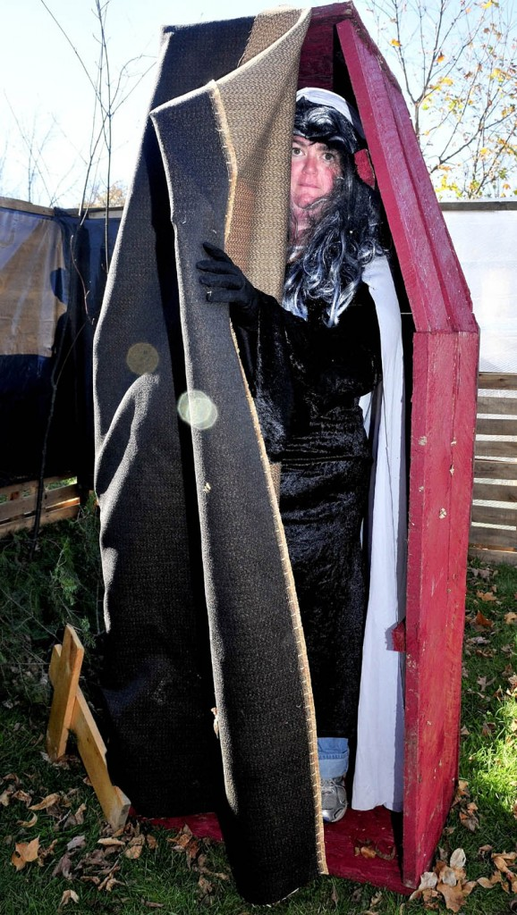 """WELCOME: Dressed as a vampire, Shannon Dunton opens her coffin in the cemetery section of the """"Nightmare on North Main Street"""" Halloween haunted trail in Pittsfield."""