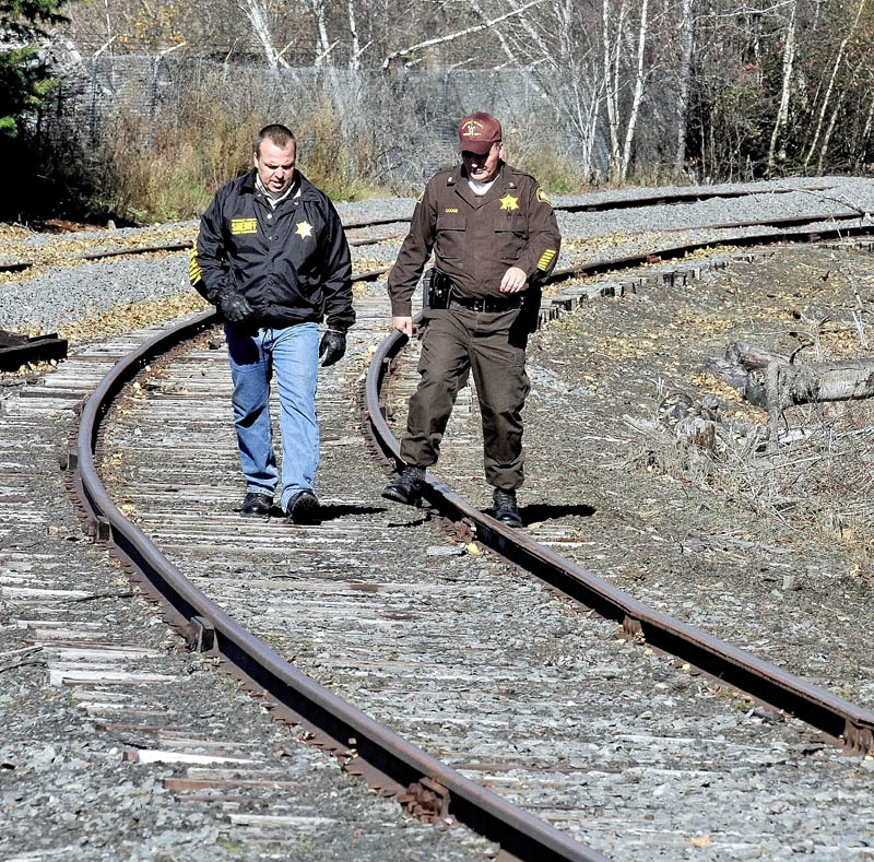 SEARCH: Somerset County Sheriff Deputies Bill Quigley, left, and Will Dodge walk along a railroad track between Union Street and the Carrabassett River in North Anson while searching for a weapon that may have been used by Randy Grover Jr. earlier in the day. Grover was arrested for domestic terrorizing.