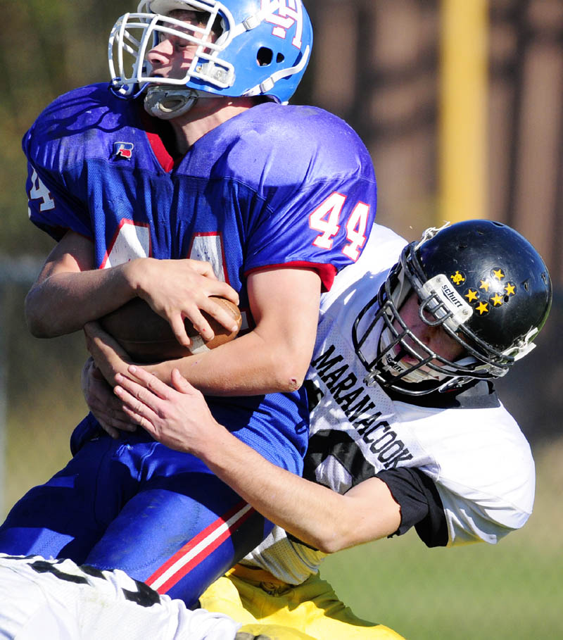 Oak Hill running back Kyle Flaherty, left, gets taken down by Maranacook defensive back Cody Lyon during a game on Saturday afternoon at Oak Hill High School in Wales.