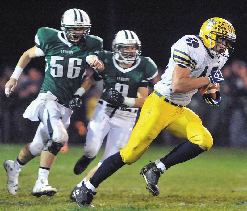 OFF AND RUNNING: Mt. Blue High School running back Chad Luker, right, breaks away from Leavitt defenders for a long touchdown run early in the first quarter Friday at Leavitt Area High School in Turner.