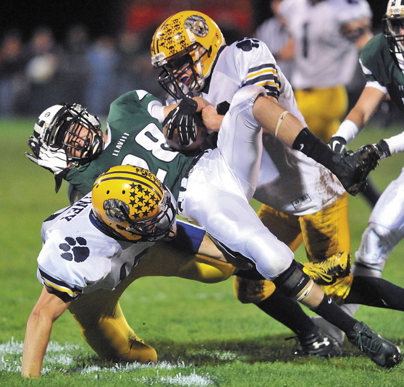 Leavitt High School's Josh Faunce, center, is sandwiched by Mt. Blue High School defenders Jordan Whitney, bottom, and Brian Durrell, top, in the second quarter at Leavitt High School in Turner Friday night. Mt. Blue lead at halftime 20-6.