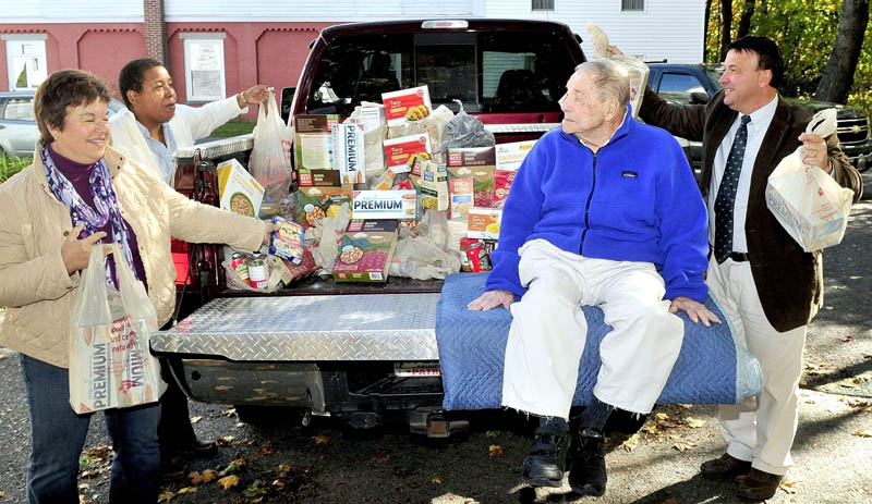 """Charlie Breton, on truck, watches as his daughter Carol Mckinnon, left, Rev. Effie McClain and son Alan Breton deliver $500 worth of food to the Oakland Area Food Pantry in Oakland on Wednesday. Charlie Breton's cousin Georgette Desmond suggested guests donate food rather than gifts during Breton's recent 94th birthday party. """"It's a much needed food donation,"""" McClain said."""