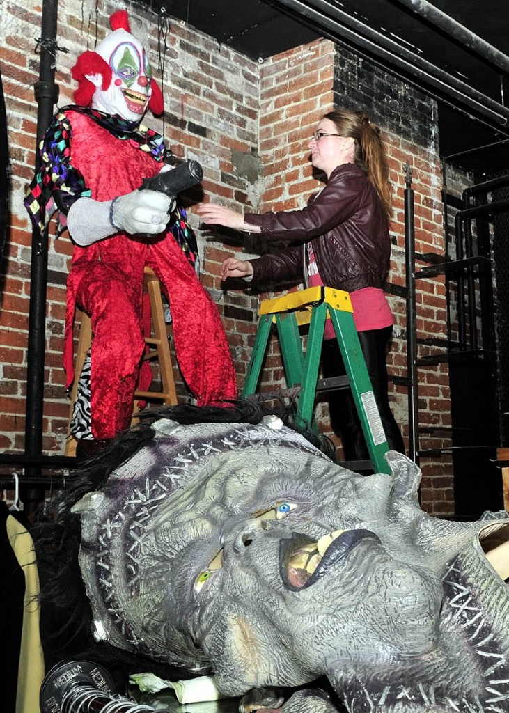 Outskirts Vintage clothing store owner Danielle Nault arranges a Halloween clown near other masks and outfits at the Farmington store on Monday. Nault said business has been brisk and there are plenty of costumes to choose from for the annual fright night.
