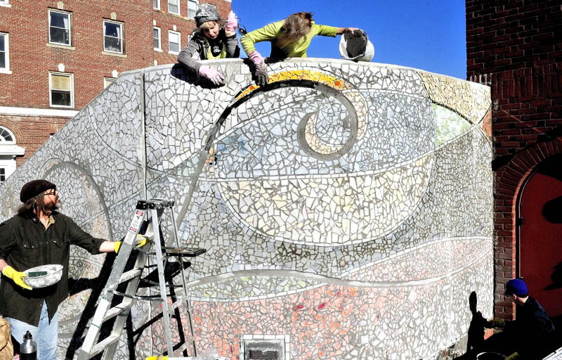 "Artists Jane Burke, left, and Gina Colombatto rub off grout from the nearly complete mosaic ""Oh! Courant"" on the stairs of the Waterville Public Library on Thursday. Michael Libby and Victoria Stubbert also work on each side. The art will be covered before being officially unveiled in November."