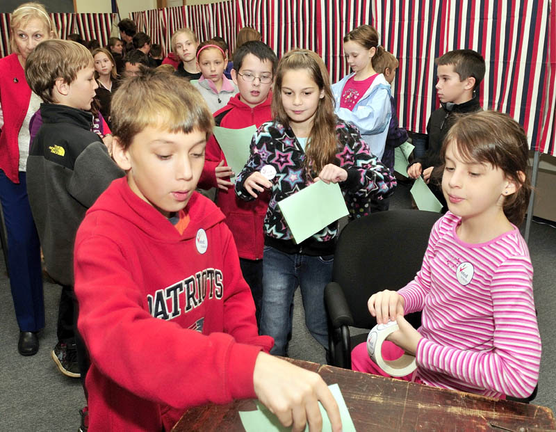 Students from the Margaret Chase Smith school in Skowhegan cast their ballots during a statewide mock election at the Municipal Office on Tuesday. Ballot clerk Alivia Rac, right, monitors as Chris Allmendinger and Emma Duffy cast their ballots. The students elected Barack Obama for president, Michael Michaud for Congress and Angus King for U.S. Senate.
