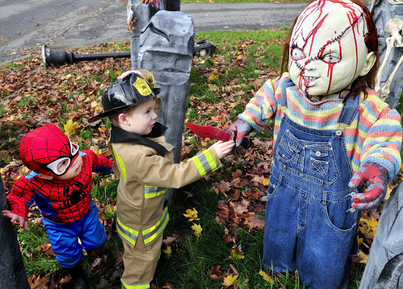 "Ben Coles, left, and Glen Carol cautiously check out the ""Chucky"" character in the Halloween display at Melissa and Jeff Giguere's home in Waterville, on Wednesday. The kids were part of a large group from the Black Bear Nursery in Waterville."