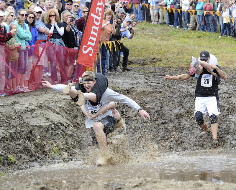 Miles and Kate Egbert of Michigan trudge through a muddy pond during the 2012 North American Wife Carrying Championship at Sunday River in Newry on Saturday. Fifty couples competed in the obstacle course.