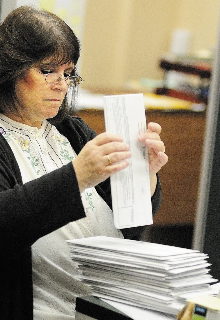Martha Burns stacks and date-stamps a stack of absentee ballots that arrived by mail at the Augusta City Clerk's Office on Thursday morning.