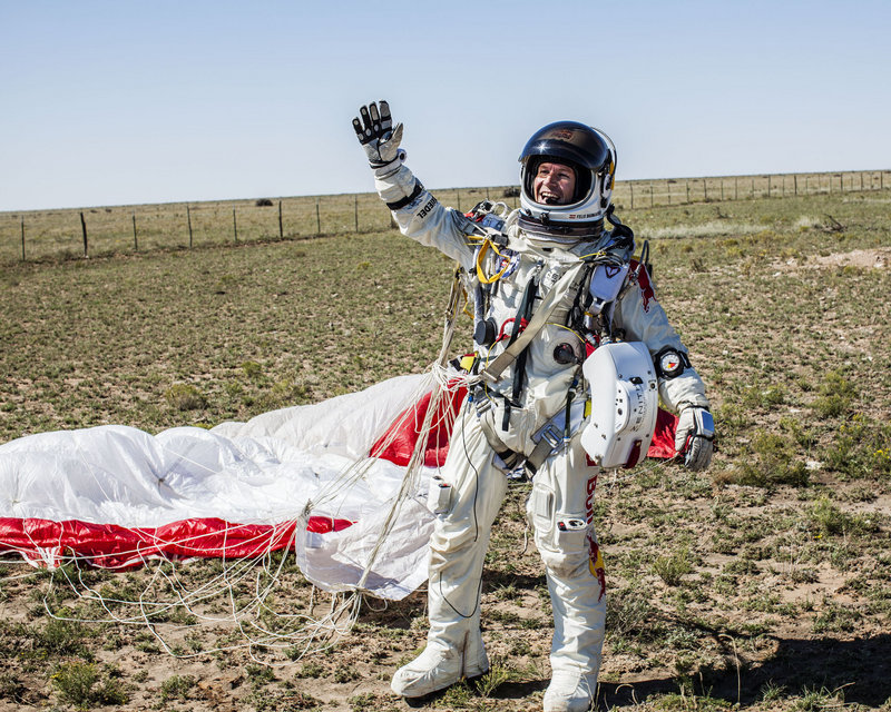 Felix Baumgartner of Austria celebrates after coming down in the eastern New Mexico desert minutes after jumping from his capsule more than 24 miles above the Earth.