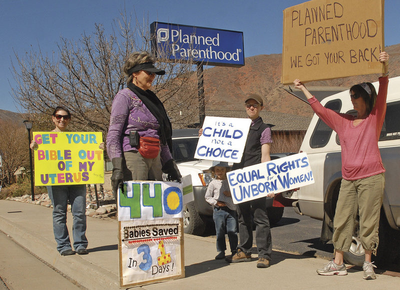 Advocates from both sides of the abortion issue share the sidewalk next to the Planned Parenthhood clinic in West Glenwood, Colo., in March.