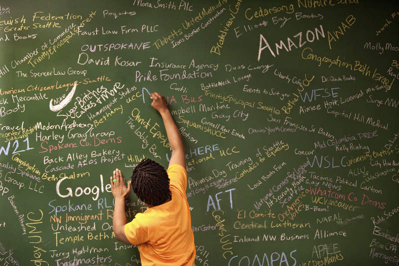 Sylvia Rolle, social-media director for Washington United for Marriage, writes the names of a few more supporters – business, labor, faith and other organizations – on the endorsement wall at the Seattle, Wash., campaign headquarters.