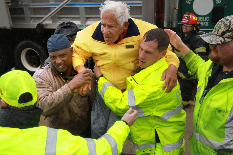 An elderly man is taken to safety by volunteer firefighters in West Atlantic City, N.J., on Monday.