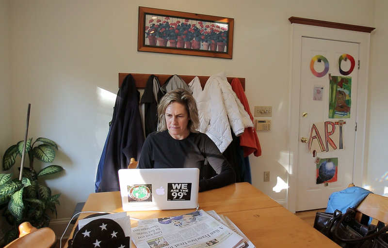 Cynthia Dill checks email on her laptop after returning home from a run in Cape Elizabeth. Each day of campaigning has been different, she says, whether traveling around the state or working from home or meeting voters at various events.