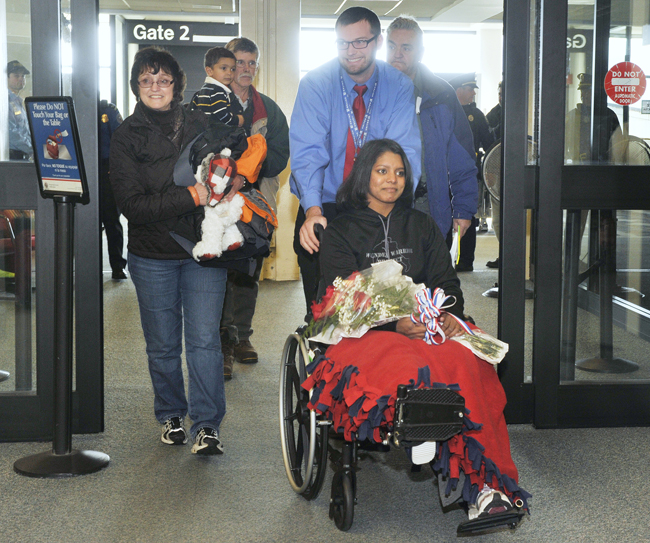 Army Sgt. Helaina Lake along with her mother, Jeannine, left, were met by family and friends as she departed the gate area at Portland Jetport on Tuesday.