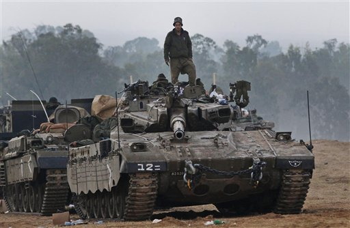 An Israeli soldier stands on a tank at a staging area near the Israel Gaza Strip Border, southern Israel, early Tuesday.