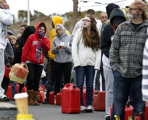 As temperatures begin to drop, people wait in line to fill gas containers at a Shell station in Keyport, N.J., on Thursday. In parts of New York and New Jersey, drivers lined up for hours at gas stations that were struggling to stay supplied.