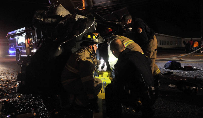 Delta Ambulance paramedics, Waterville police officers and the Waterville Fire Department work to extract at least two people from a Jeep that struck a treee off College Avenue in Waterville on Thursday night.