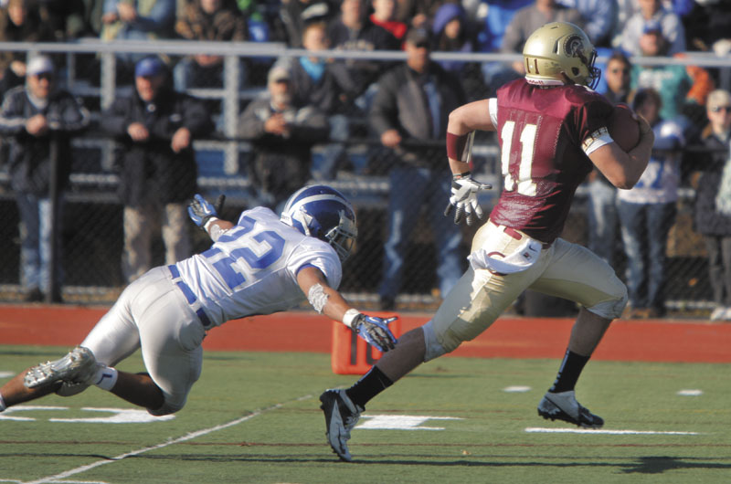 Thornton Academy quarterback Eric Christensen pulls away from Xavier Lewis of Lawrence to score a touchdown in the third quarter for the Trojans in the Class A state football championship on Saturday at Fitzpatrick Stadium in Portland. Thornton won, 37-23.