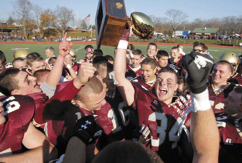 Senior Nick Kenney of Thornton Academy hoists the championship trophy after the Trojans defeated Lawrence, 37-23, to win the Class A state football championship on Saturday at Fitzpatrick Stadium in Portland.