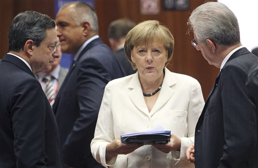 German Chancellor Angela Merkel, center, speaks with European Central Bank President Mario Draghi, left, and Italian Prime Minister Mario Monti during a round table meeting at a EU Summit in Brussels in June.