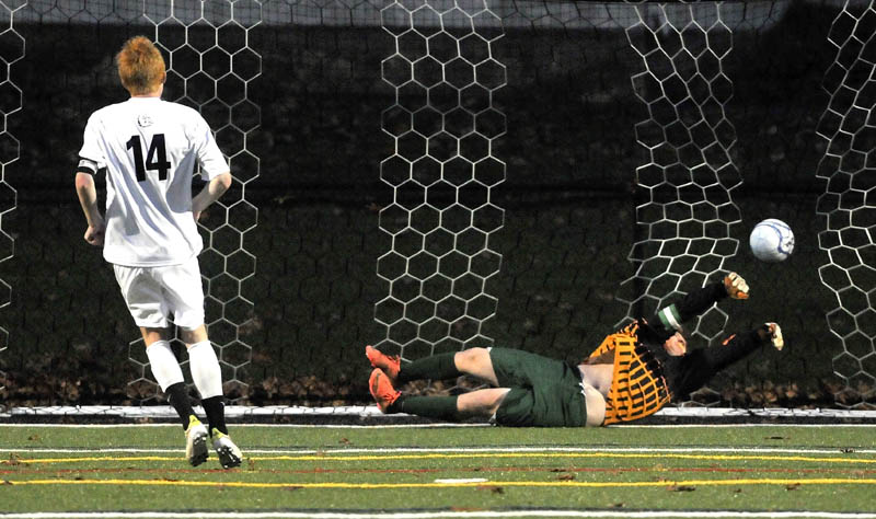 GAME-WINNER: Hall-Dale High School's Colin Lush (14) scores the game-winning goal in a penalty kick shootout past Waynflete goalie Zander Majercik during the Western Maine Class C boys soccer championship game Thursday at Thomas College in Waterville. Hall-Dale won the shootout 5-4 and the game 1-0.