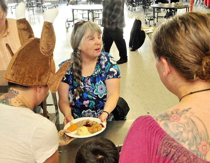 Sally Dill, center, takes her Thanksgiving dinner back to her seat on Thursday morning at Gardiner Area High School.