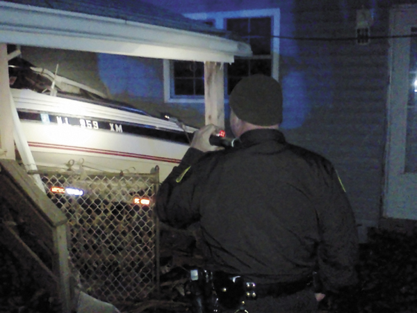 Cumberland County sheriff's Sgt. James Ambrose inspects a boat in Monmouth County, N.J., that was washed onto a house porch by Superstorm Sandy. Ambrose and contingent of Maine troopers and deputies are helping local police there patrol the streets and enforce a 6 p.m. to 6 a.m. curfew.
