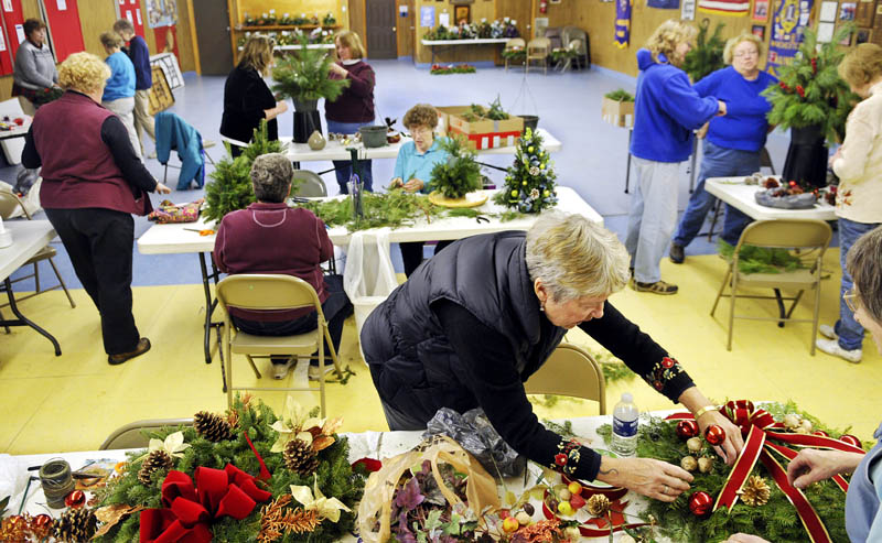 Volunteers assemble evergreen floral centerpieces, decorate boxwood trees and wrap wreaths Thursday at the Manchester Lions Club. More than 50 people from a variety of community groups are assembling the holiday floral designs to be auctioned off Sunday at Manchester's annual fuel assistance fundraiser at the elementary school. The 2 p.m. auction will be followed a tree lighting ceremony. All proceeds will be donated to winter heating fund for Manchester residents.