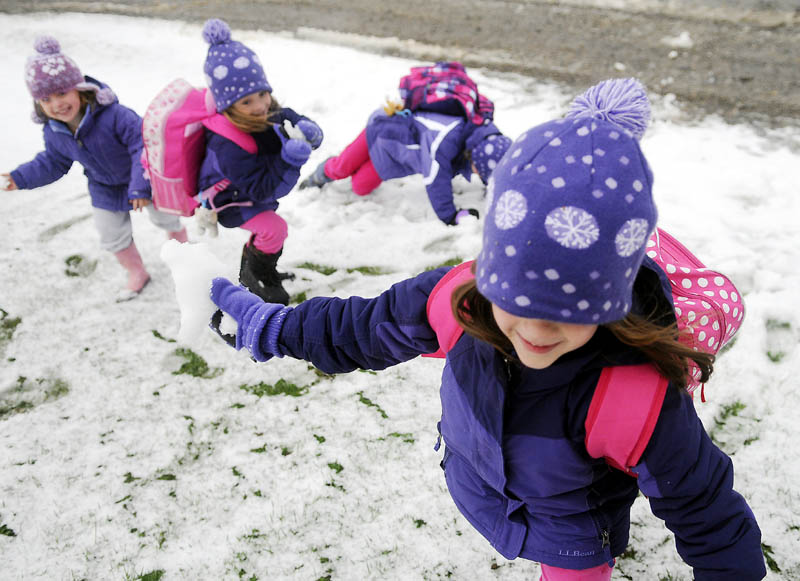 Abby Perry, 5, winds up to deliver a snowball Thursday while brawling with her twin sister, Emma, second from left, and cousins, Marinn Perry, 4, left, and Grace Perry, 6, at their grandparents' Hallowell farm. The children were waiting for a bus to deliver them to school that was delayed two hours by the first snowfall of the season.