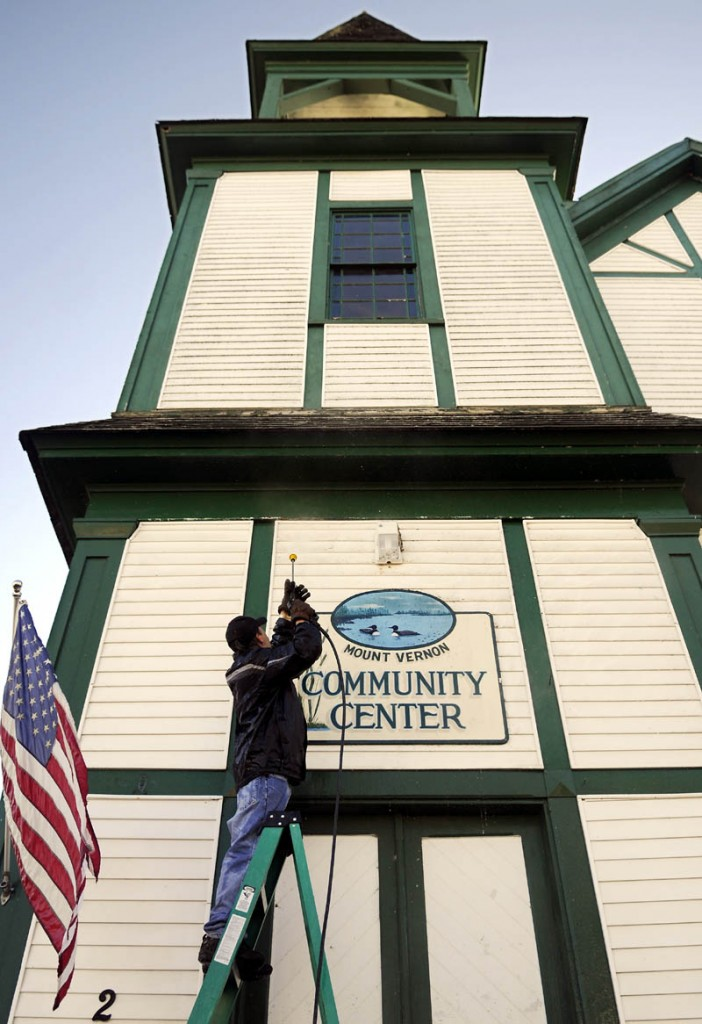 """Darrell Trask, of Vienna, sprays the exterior Wednesday of the Mount Vernon Community Center, on the shores of Minnehonk Lake. The proprietor of Sunny Day Cleaning said he was soaked from pressure washing the first level of the decommissioned church which is open for town events. """"I'm hurrying up because I'm freezing,"""" Trask said."""