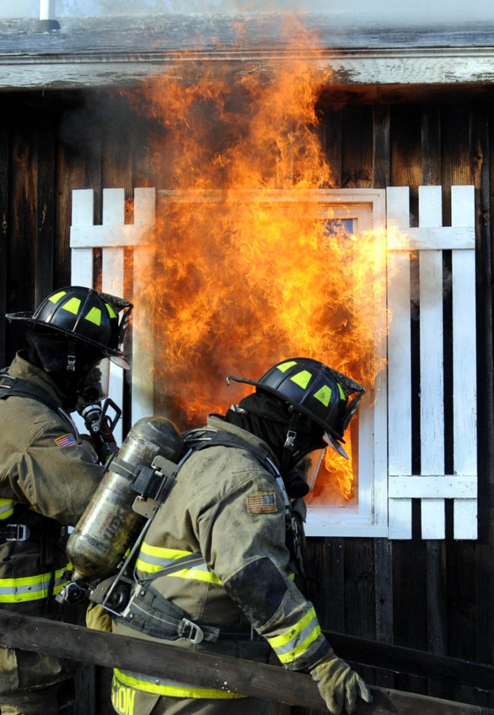Firefighters walk past a burning window Sunday during a controlled burn of a donated home and barn at the Kelley Bros. Farm in Pittston. Dozens of firefighters from communities in Lincoln and Kennebec County practiced extinguishing blazes and rescuing trapped people during the exercise, Pittston Fire Chief Jason Farris said.
