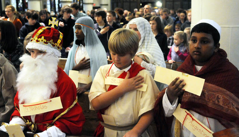 St. Michael School fifth graders bless themselves during a service Thursday at St. Mary's Church in Augusta on All Saints Day. Children from the private school dressed as saints during the annual Mass to celebrate individuals canonized by the Catholic Church.