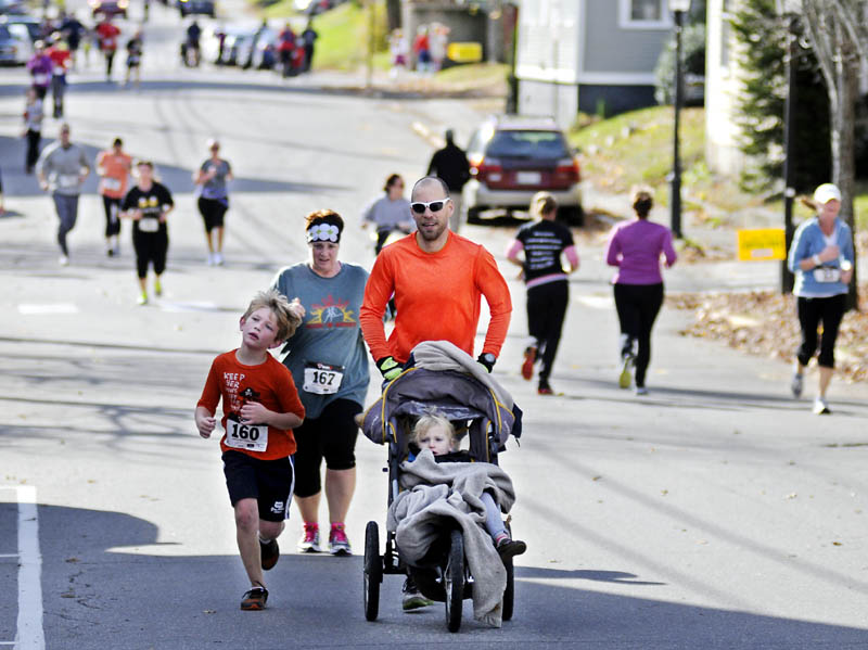 Hall-Dale Elementary students, parents, faculty and staff run down Second Street in Hallowell on Sunday during the inaugural Sugar Rush 5K. The parent-teacher organization hosted the walk and jog to raise funds for the school and donate extra Halloween candy to Operation Gratitude, which delivers sweets to troops serving abroad.