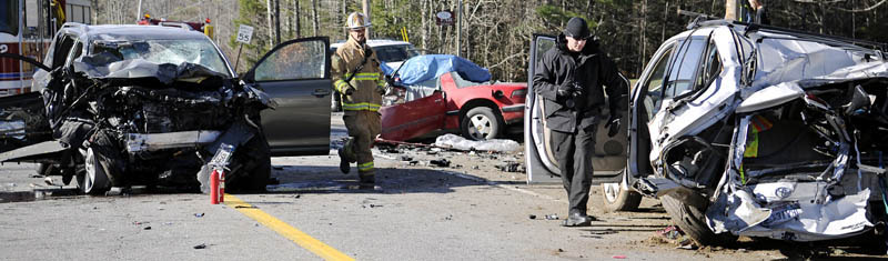 Augusta Fire Chief Roger Audette, left, and Kennebec County Sheriff's Sgt. Mike Pion move among the wreckage of three vehicles that collided Thursday morning on Route 17 in Windsor, claiming the life of one man and injuring four people.