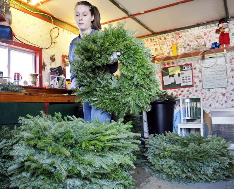 Crystal Gatcomb stacks a wreath she wrapped Monday with her grandmother, Darlene Ames, at the latter's evergreen bough decoration business in Fayette. Mountain View Wreath Shop creates several thousand of the Christmas adornments between November and Christmas, according to Ames.