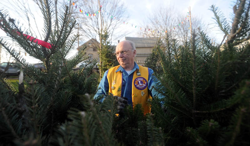 Ray Watson, 68, of Oakland, and a member of the Oakland Lions Club, arranges Christmas trees for sale on Kennedy Memorial Drive in Oakland. Proceeds help purchase warm clothes and toys for disadvantaged children in the area.