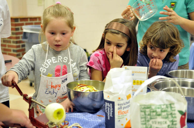 Hannah Robertson, 6, right, and Lynzi Trepanier, 6, center, watch as Abbigail Kolreg, 6, left, peels an apple with a mechanical peeler as the girls prepare apple pies in the cafeteria at Messalonskee High School on Tuesday. Girl Scout Troop 1989 has been preparing pies for the community Thanksgiving dinner at Messalonskee High School since 1997.