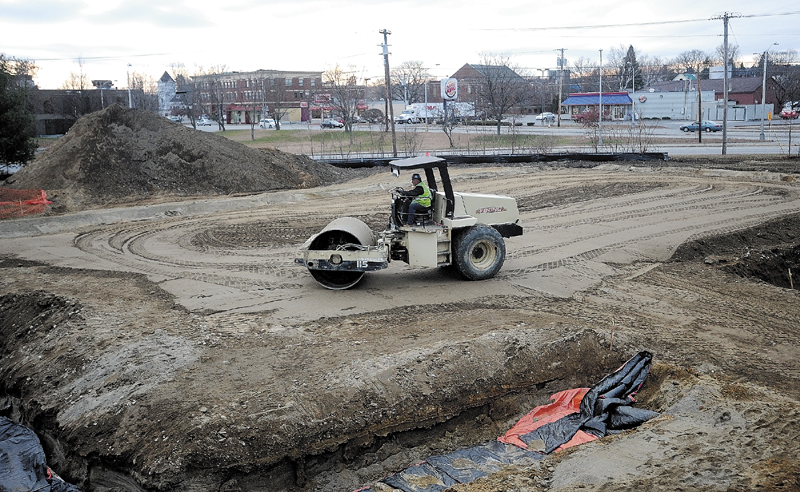 Construction workers level the ground of the new Waterville police station site for a foundation, at Colby Circle in Waterville, on Tuesday.