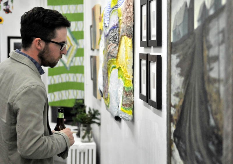 Zach Vickers, of Coopers Mills, looks at art work at Common Street Arts in Waterville during the opening of a new exhibit, featuring a collection of art inspired by local farms over the last growing season, on Saturday.