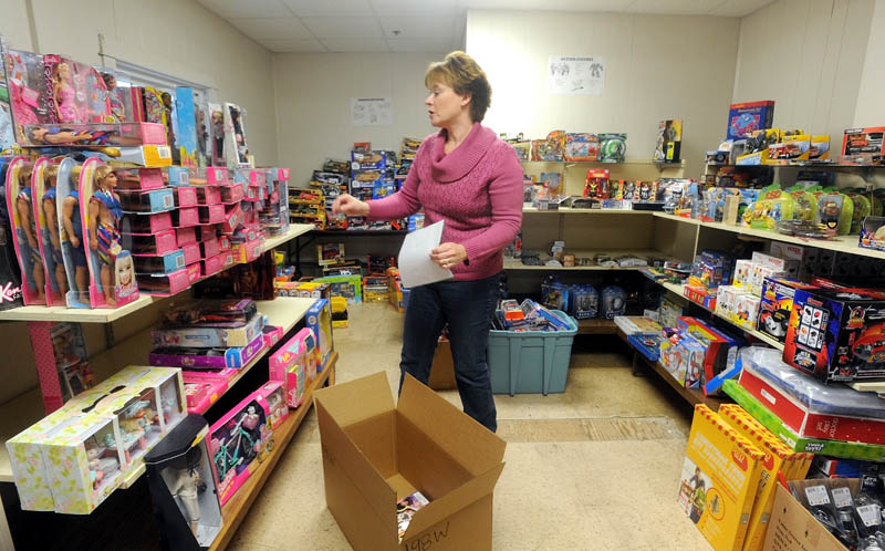 Christen Sawyer, the Christmas program director at Maine Children's Home for Little Wanderers in Waterville, prepares Christmas gift boxes for children in need in the central Maine region.