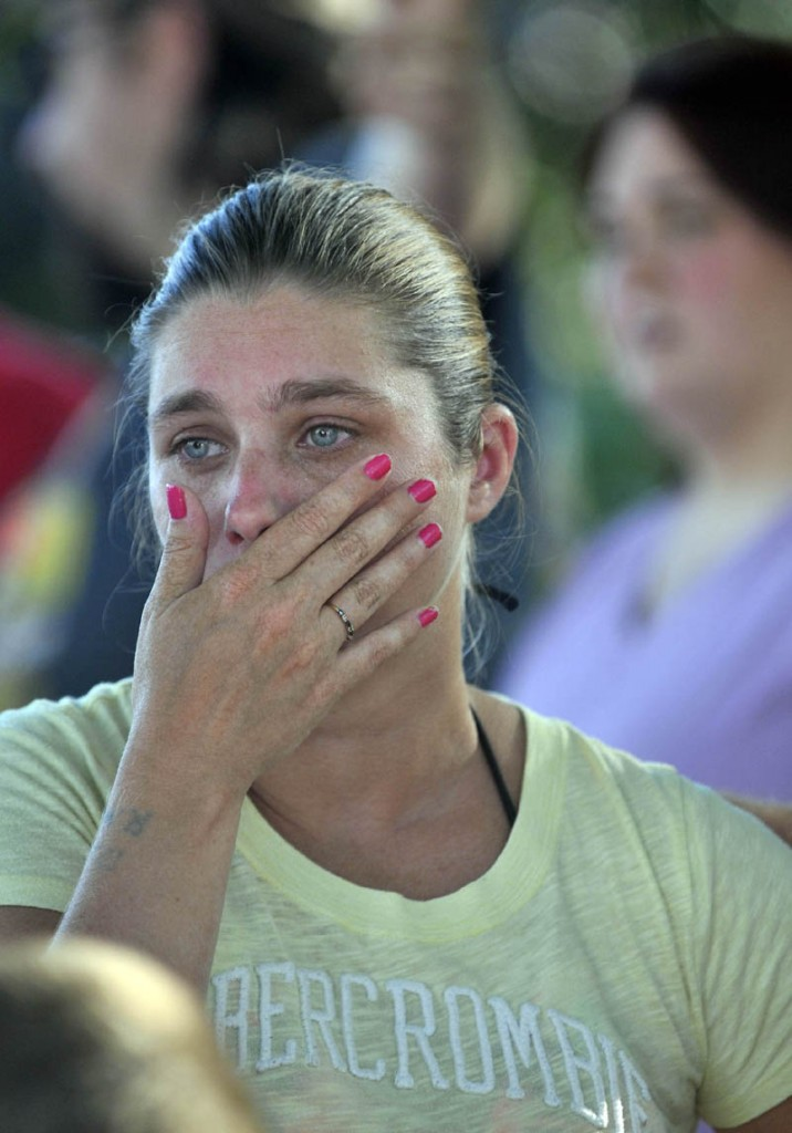 Janet White wipes tears from her cheek as Waterville firefighters battle a blaze that engulfed her apartment building on the corner Drummond Avenue and Spruce Street in Waterville.
