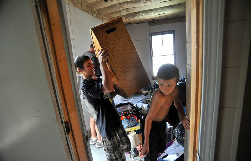 Rusty Wing, 14, left, and his step-brother, Dakota LaBrie,11, organize donated goods from charities at their new apartment on King Street in Waterville.