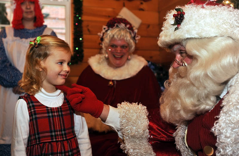 Hannah Rauch, 3, smiles as Santa Claus says hello, at Kringleville in Castonguay Square in downtown Waterville, on Saturday.