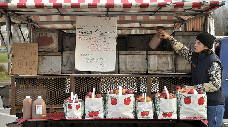 Jessica Sueiro, of Boston, stocks cider and apples on the Trask Orchard truck on Main Street in Farmington Friday afternoon. Sueiro said her parent's have owned the orchard for more than 45 years and she travels to Farmington each weekend to help out.