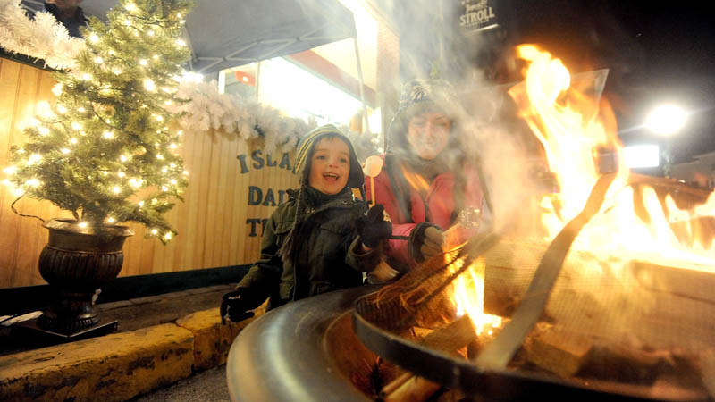 Christina Easler, right, and her son, Gavyn, 4, enjoy a hot marshmallow over an open fire on Water Street, at the Holiday Stroll parade on Water Street in downtown Skowhegan, on Friday.