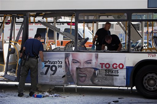 Israeli police officers examine a blown-up bus in Tel Aviv Wednesday. The blast near Israel's military headquarters wounded 27 people.