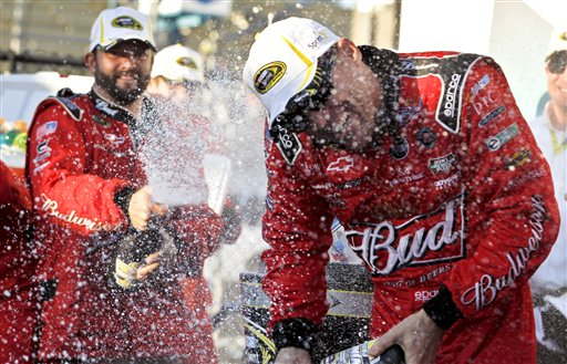 Kevin Harvick laughs as he tries to avoid being sprayed while celebrating in victory lane with his pit crew after his win at the NASCAR Sprint Cup Series auto race win at Phoenix International Raceway, Sunday, Nov. 11, 2012, in Avondale, Ariz. (AP Photo/Ross D. Franklin)